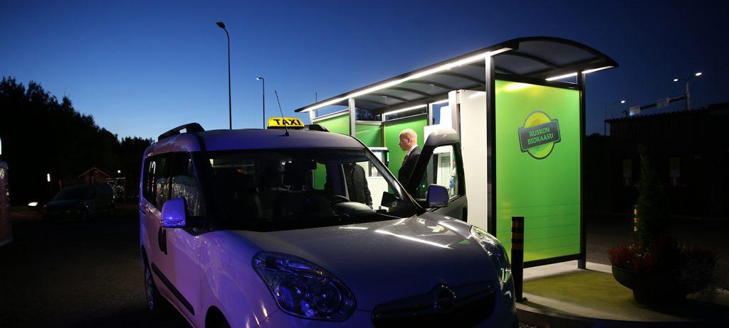 Taksinkuljettaja tankkaa biokaasua taksiin illan hämärässä.