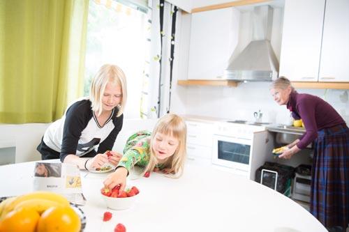 Lapset syövät mansikoita keittiössä ja isoäiti laittaa jätteitä biojäteastiaan.